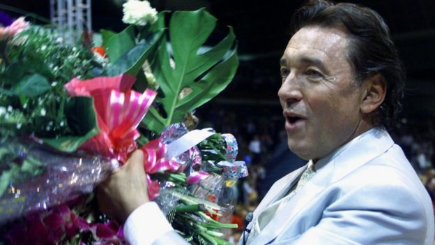 Karel Gott carries flowers from the stage during a Gala Show on his 60th birthday in Prague Sports Hall in 1999
