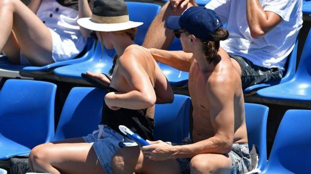 Person applying sun cream to another person