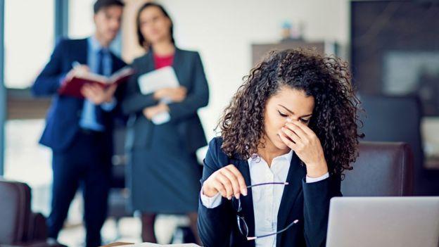 Mujer preocupada en la oficina, con dos colegas al fondo