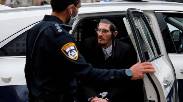 Un policía detiene a un ultraortodoxo en Me'a She'arim, Jerusalén.