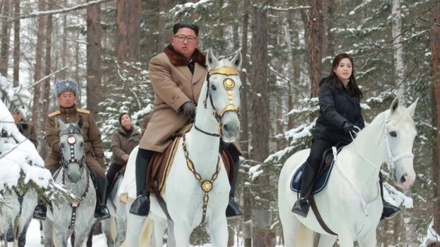 Kim Jong-un and his wife and officials riding horses through the snow in North Korea