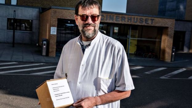 Un médico en Dinamarca con una caja con Remdesivir.