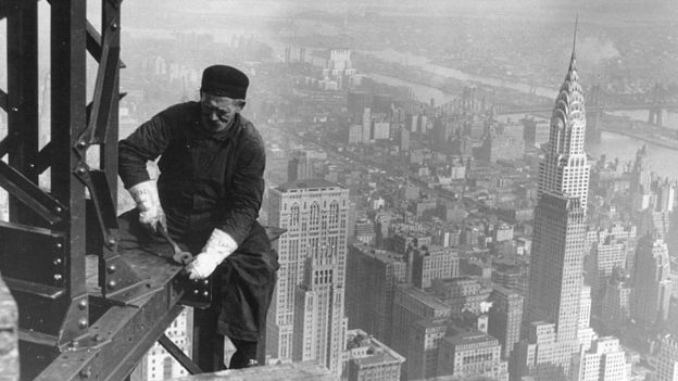 Un obrero trabaja desde las alturas en la construcción del Empire State, con el edificio Chrysler de fondo.