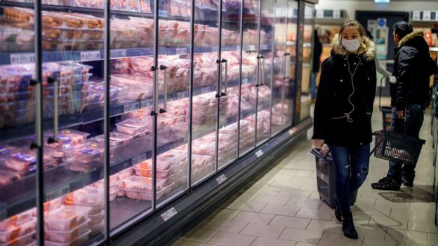 Person in a facemask walking past supermarket freezer