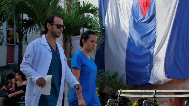 Dois profissionais de saúde caminham em frente a uma bandeira cubana no hospital Calixto Garcia, em Havana