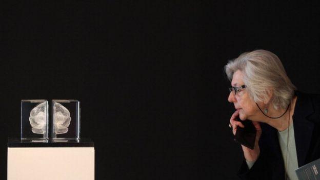 Mujer observa un cerebro en una urna
