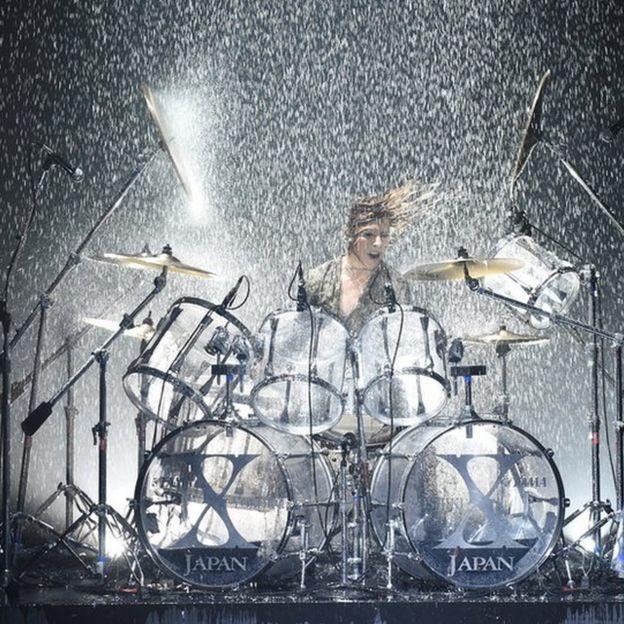 ずぶ濡れでドラムを叩くyoshiki