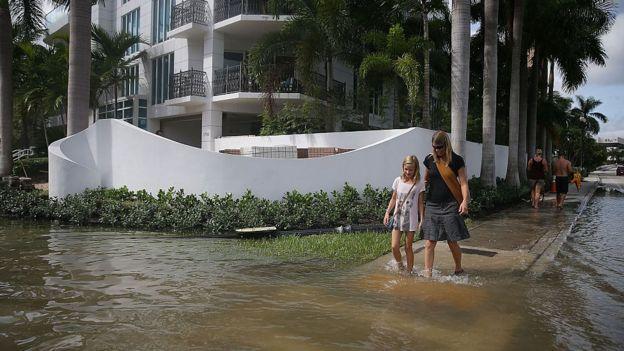 Unas personas caminan por una calle inundada de Fort Lauderdale.