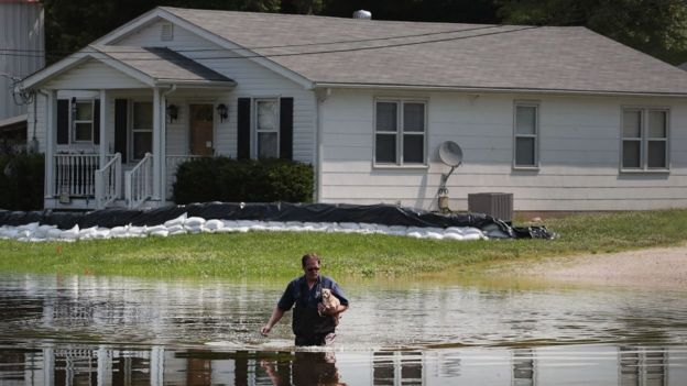 A man walks through floodwater from the the Mississippi River as he leaves his home with his dog Tiny