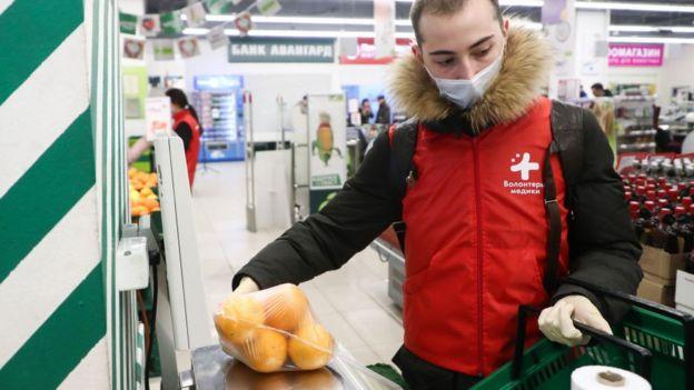 Un joven voluntario ruso hace la compra