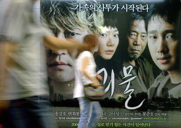 """Una mujer pasa frente a una valla publicitaria de la película """"The Host"""" en Seúl"""