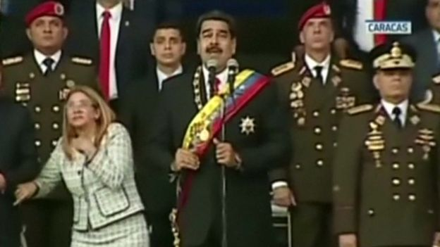 President Maduro (centre) and his wife Cilia Flores (left) react to a loud bang during the military event
