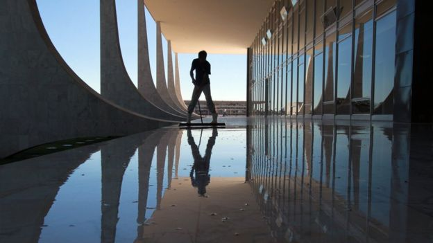 Sombra de pessoa limpando chão da varanda do prédio do STF durante o dia