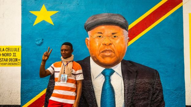A supporter of veteran opposition chief Etienne Tshisekedi poses for a photograph with his portrait front of his residence in Kinshasa, on July 27, 2016. Etienne Tshisekedi,