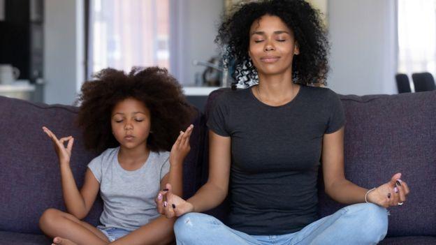 Una mujer y una niña meditando