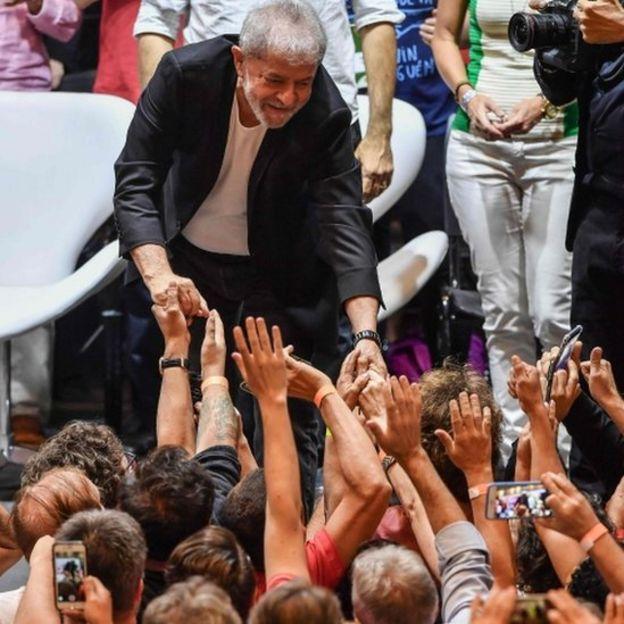 Ex-presidente Lula dá a mão para público