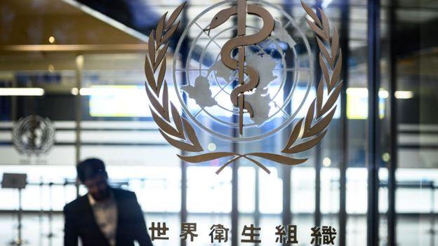 Homem passa por emblema da Organização Mundial da Saúde (OMS) no vidro de prédio na Geneva