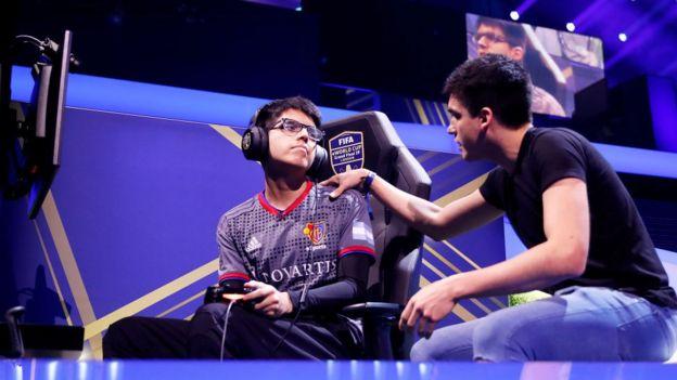 Un entrenador habla con un jugador de videojuegos