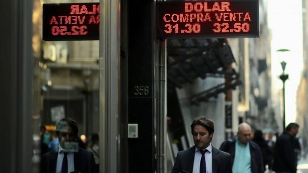 """People walk past an electronic board showing currency exchange rates in Buenos Aires"""" financial district, Argentina August 29, 2018"""