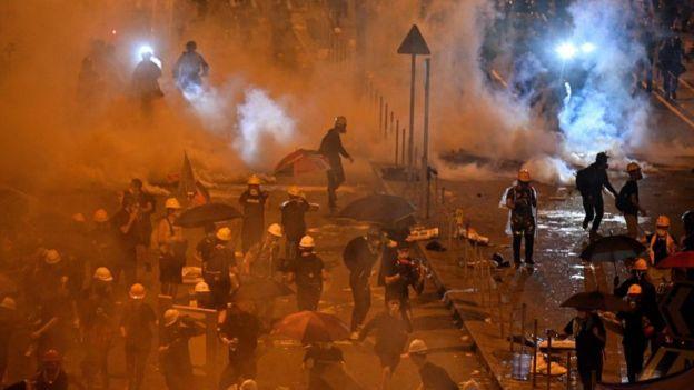 Policía disparando gas lacrimógeno.