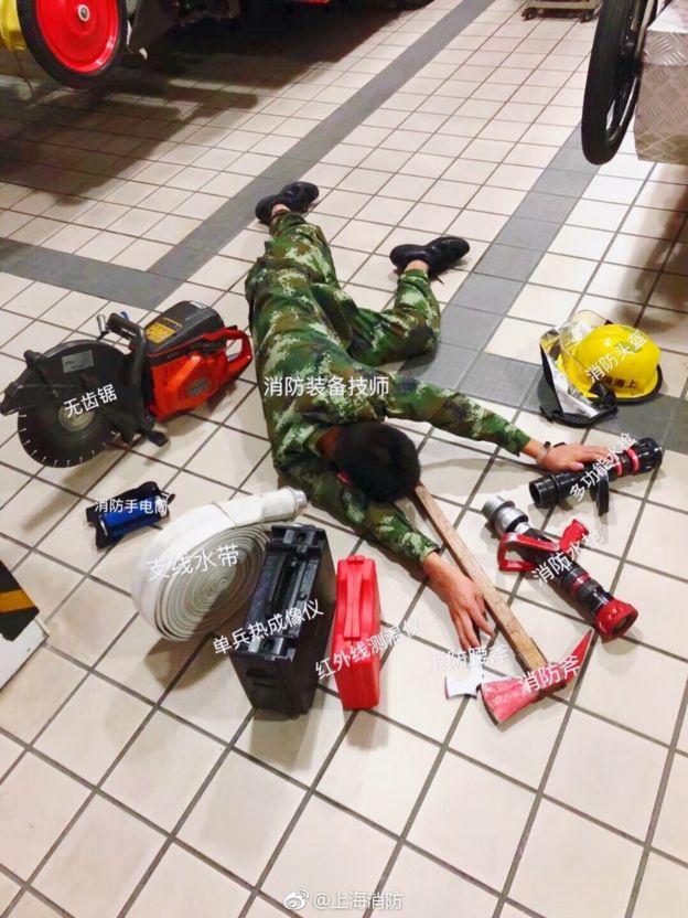 上海消防局發佈的微博顯示,一名消防裝備技師倒在了消防斧、消防頭盔等一堆工具旁邊。