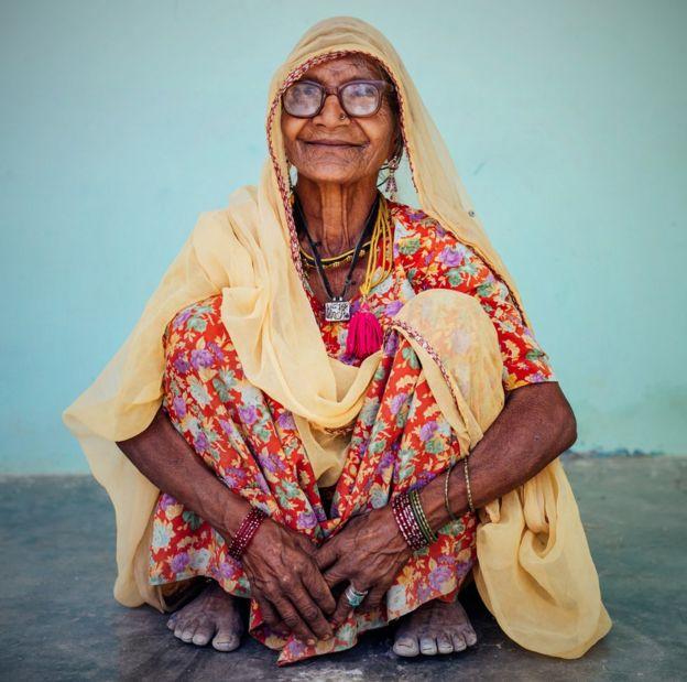 Anciana india sentada en cuclillas.