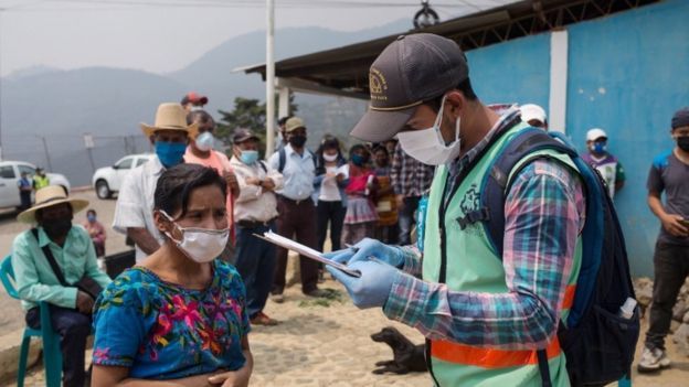 People wait in line to receive aid supplies from the municipality after the restriction measures ordered by the government to prevent the spread of coronavirus at El Hato, in Antigua Guatemala, Guatemala, 25 April 2020.