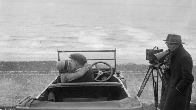 A couple in an open car locked in a passionate embrace for a scene in the film, The Thrill, being shot in 1926