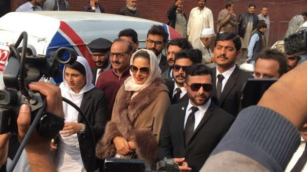Meera surrounded by journalists and employees