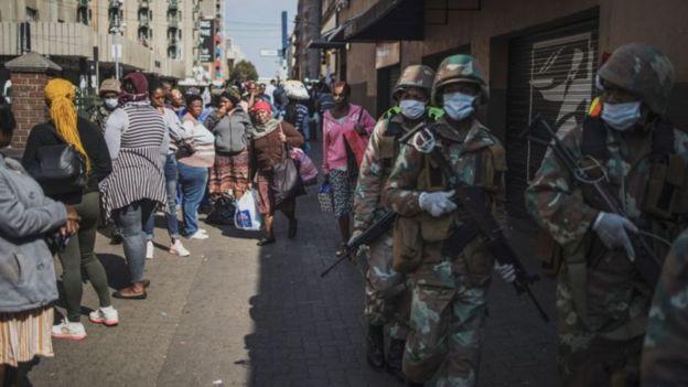 Soldados armados e vestindo máscaras cirúrgicas e luvas patrulham rua cheia de civis