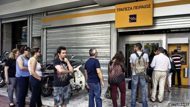 People waiting in line to withdraw money from an ATM in Greece