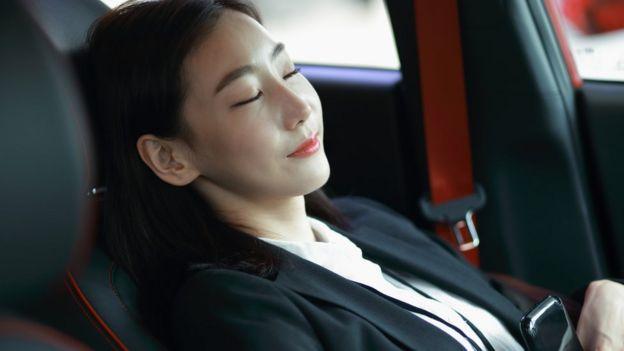 Mujer dormida placenteramente dentro de un vehículo.
