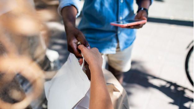 Entregador dá pacote a cliente
