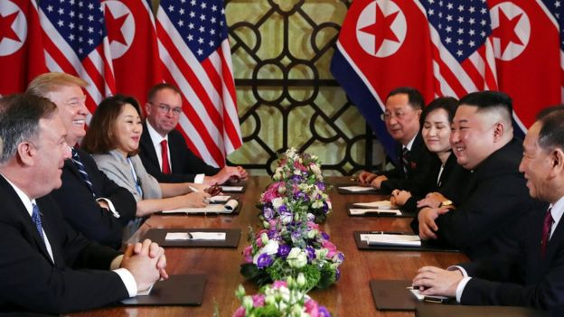 Trump and Kim sitting across from each other at Vietnam summit