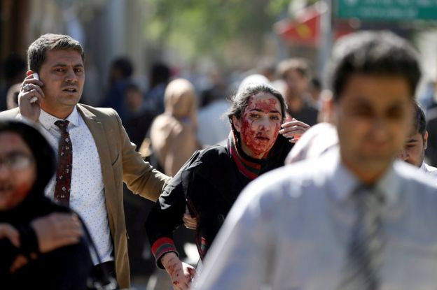 Injured Afghans run from the site of a blast in Kabul, Afghanistan 31 May 2017.