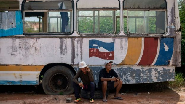 Dois venezuelanos sentados em frente a ônibus deteriorado em Roraima