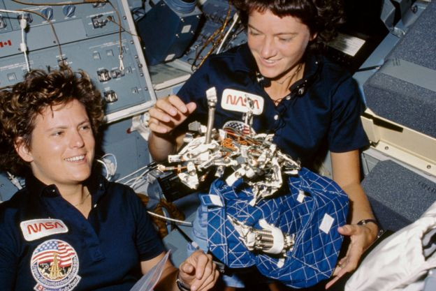"""Astronauts Kathryn D. Sullivan, left, and Sally K. Ride display a """"bag of worms."""" The """"bag"""" is a sleep restraint and the majority of the """"worms"""" are springs and clips used with the sleep restraint in its normal application"""