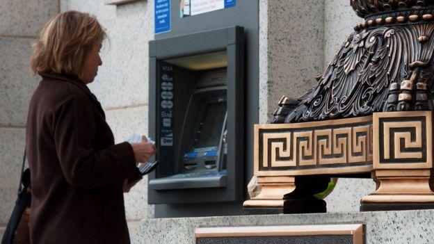 Una señora saca dinero de un cajero de Bank of America