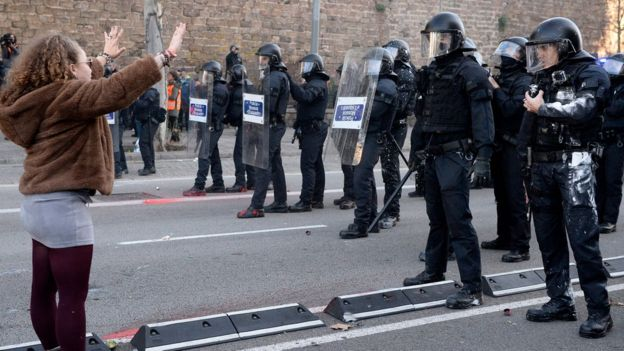 A woman gestures opposite members of the Catalan regional police force in Barcelona on December 21, 2018