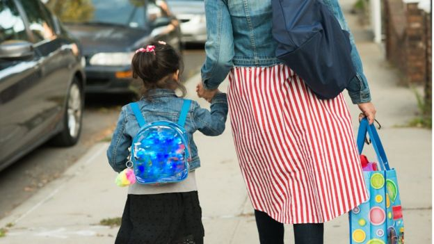 Mother and daughter walking to school stock photo
