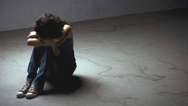 Adolescente sentada en solitario.