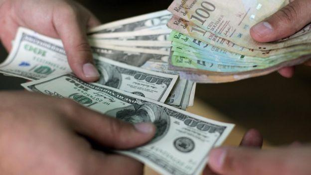 Más que usarse dólares, estos se cambian por bolívares en el mercado negro. Foto: AFP
