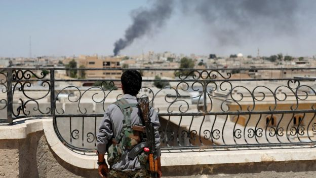 Rakka'da ABD uçaklarının vurduğu noktaları Suriye Demokratik Güçleri'nden bir militan izliyor.