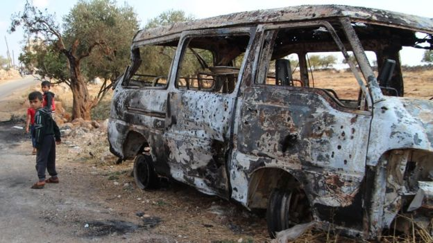 Anak-anak Suriah di dekat minibus yang terbakar akibat serangan AS di dekat desa Barisha (27/10).