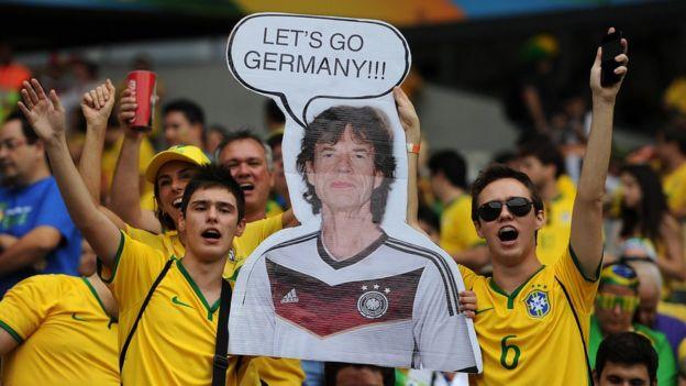 Hinchas de Brasil con una pancarta de Mick Jagger con la camiseta del equipo de Alemania.