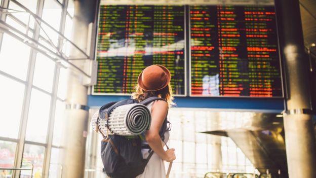 Viajera mirando la información sobre las llegadas y salidas de vuelos en un aeropuerto.