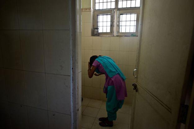 Una niña se lava en una estación de policía después de ser rescatada de unos traficantes.