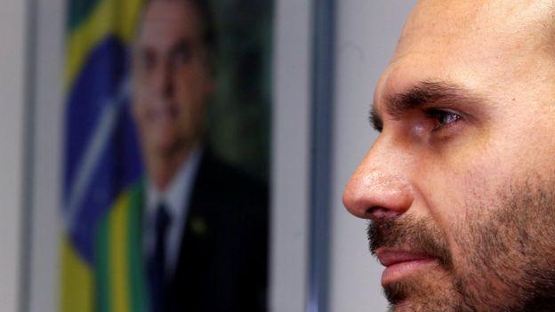 Eduardo Bolsonaro aparece de perfil com foto do pai, Jair Bolsonaro, atrás