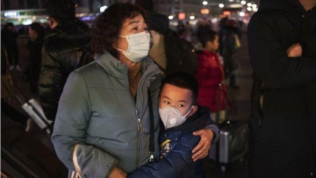Mãe e filho chineses com máscara