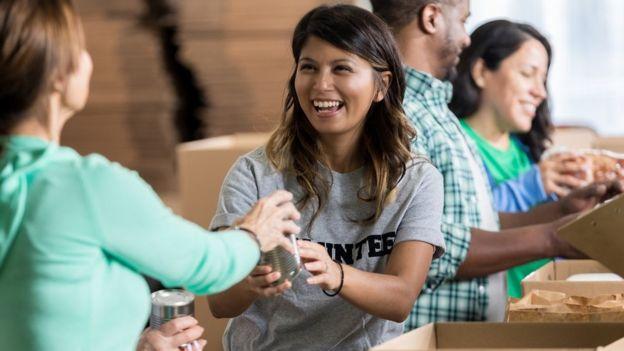 Una voluntaria alegre acepta una donación de comida enlatada durante la campaña de comida comunitaria.